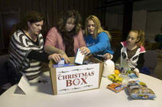 Carla Berry, Staci Pearman, Cainnamon Lyons and Carleigh Loden pack a box of food at Crossroads Family Church in Portage Wednesday Dec. 19, 2012.
